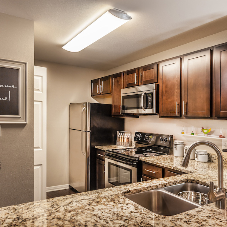 Spacious kitchen with granite counter tops, dark wood cabinetry, and stainless steel appliances